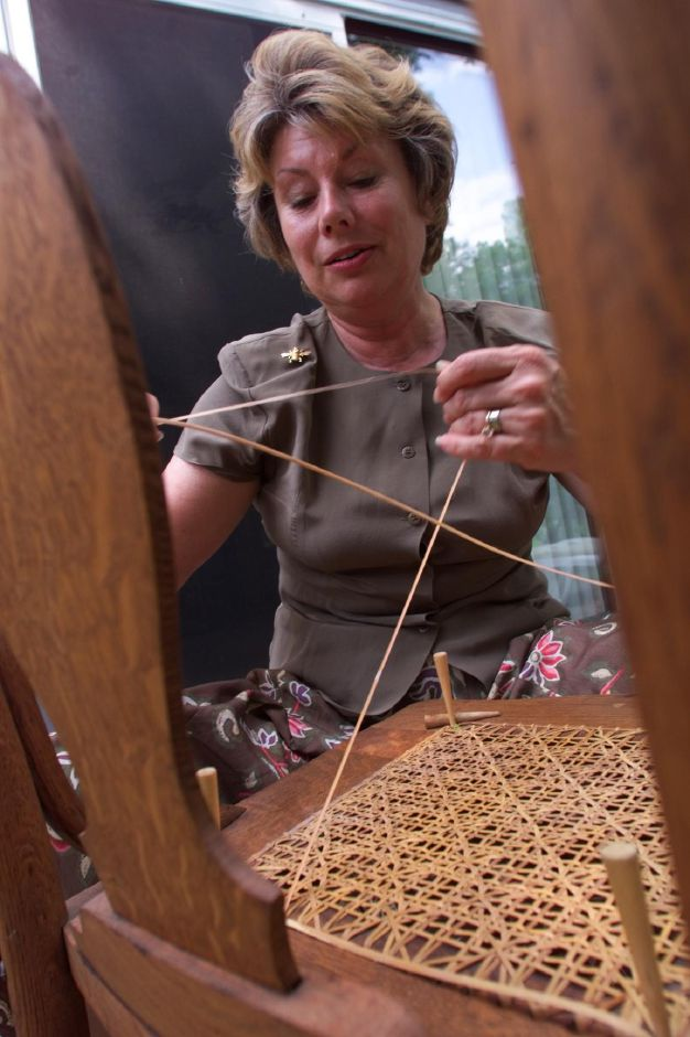 Carol Dragon , seat weaver, applies the finishing binding on an antique chair at her Southington home, June 1999.