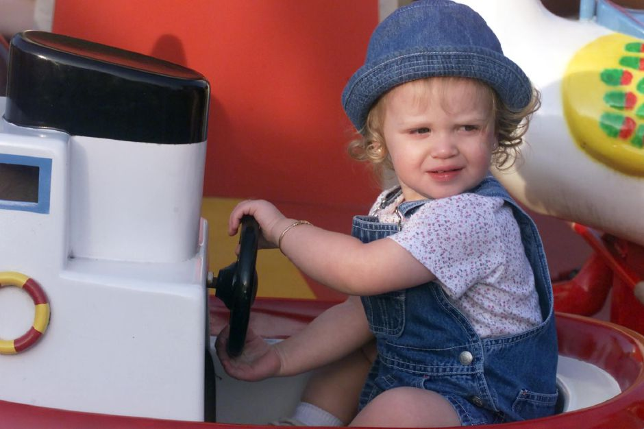 McKensi Gudrian, 17-months-old, pilots her tug boat in a kiddy ride at the 30th annual Holy Trinity Bazaar Thurs., June 8, 2000 in Wallingford.