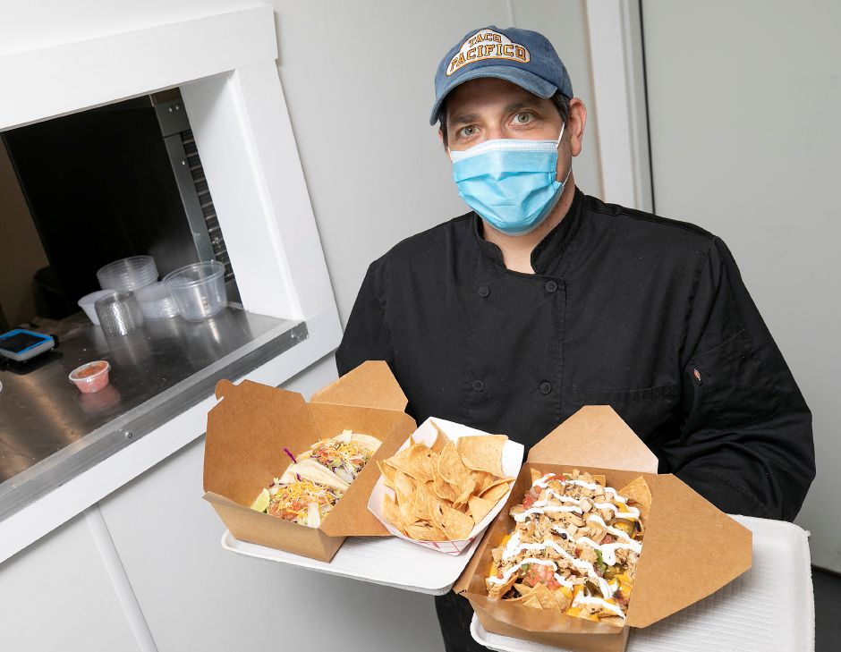 Greg Sharon, owner of Taco Pacifico, holds menu items, left to right, Barbacoa taco plate, tortilla chips with salsa fresca and grilled chicken nachos at the new 97 Chapel St. takeout business in Yalesville, Wed., Sept. 30, 2020. Dave Zajac, Record-Journal