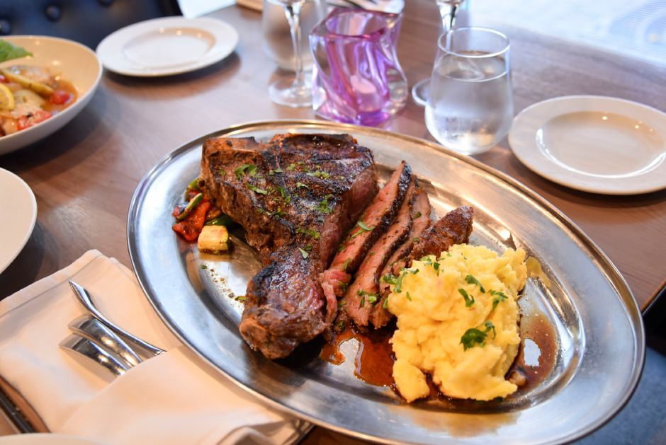 A couple of the dishes served at Nataz-  a porterhouse with mashed potatoes and Signature Salad.