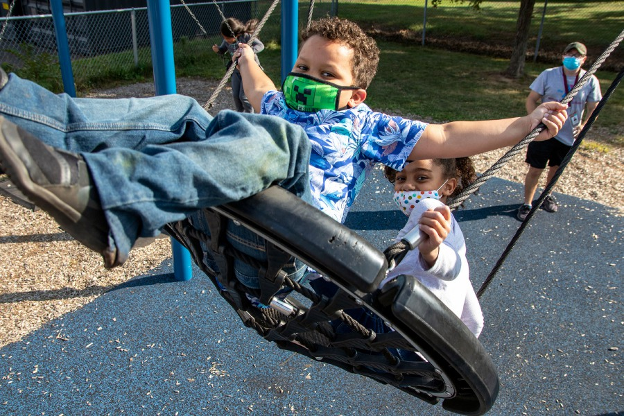 Six-year-old first-graders Christian Lewis, left, and Evelyn Bogle get a push on the swing from staff member Logan Smith during after-school care at the Israel Putnam Elementary School in Meriden on Tuesday, Sept. 22. Photos by Aaron Flaum, Record-Journal