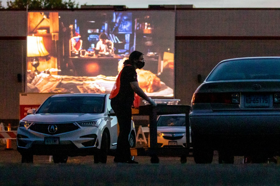 "Berlin Picture Show employee Mia Servidone delivers a food order to a car during the showing of ""Gremlins"" at the Berlin Picture Show ""Pop-up"" Drive-in on Sunday. Drive-in customers put their orders through the drive-in theater's website www.pictureshowent.com and have them delivered to their cars. Photos by Aaron Flaum, Record-Journal"