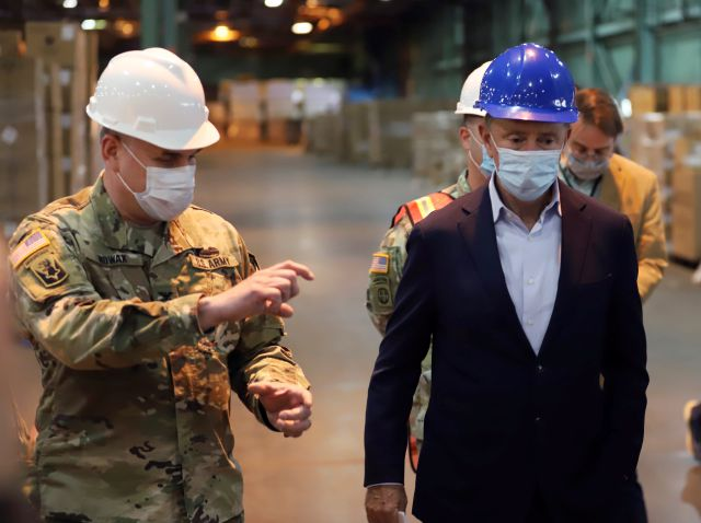 Connecticut National Guard Col. Craig Nowak, left, walks with Connecticut Gov. Ned Lamont at a New Britain, Conn., facility, that houses millions of pieces of personal protective equipment shipped from China to be used in the state