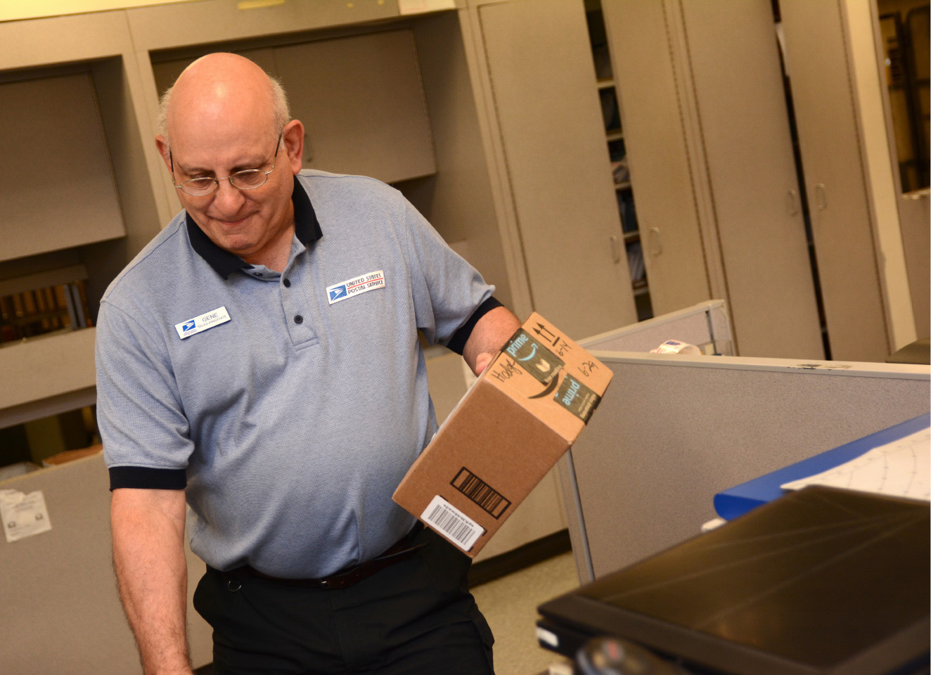 Meriden United States Postal Service clerk Gene Kirstens carries a package at the post office on Thursday, June 15, 2017. | Bryan Lipiner, Record-Journal