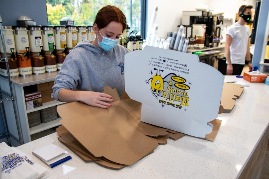 Madison Dudley, of Middletown, puts boxes together at Neil's Donuts during a soft opening at their new Middletown location on South Main Street on Thursday, October 29, 2020. Aaron Flaum, Record-Journal