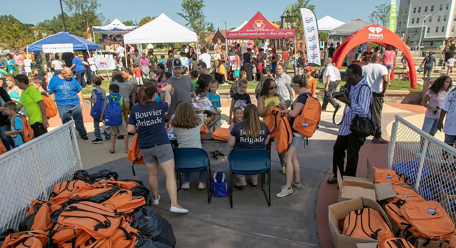 Employees from West Hartford based Bouvier Insurance help hand out backpacks during the Meriden Fire Local 1148 annual Back-to-School Expo on the Meriden Green, Tues. Aug. 20, 2019. Dave Zajac, Record-Journal
