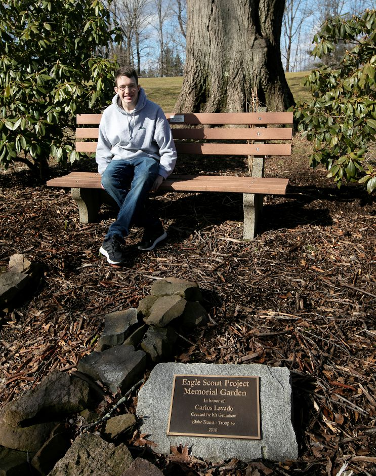 Blake Kunst, of Meriden, sits on a bench in a memorial garden he created in honor of his grandfather Carlos Lavado at Hunter Golf Course.Dave Zajac, Record-Journal