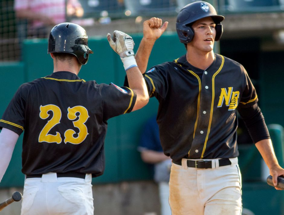 Kyle Brennan (23) greets Todd Peterson at home after he scored against the Worcester Bravehearts during the New Britain Bees' home opener at New Britain Stadium in the Futures Collegiate Baseball League. Aaron Flaum, Record-Journal