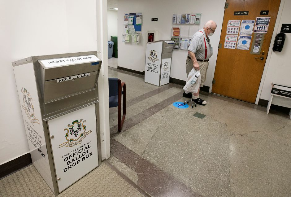 A man walks by official ballot drop boxes next to the Town Clerk office on the first floor of Wallingford Town Hall, Tues., Jul. 21, 2020. Dave Zajac, Record-Journal