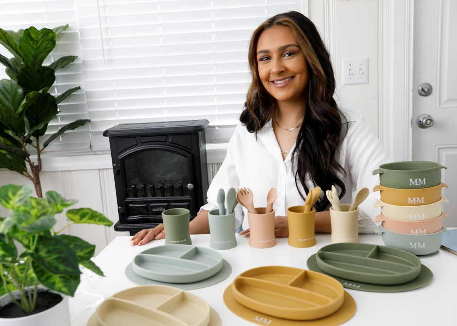 Taira Cominsky, owner of Modern Mama in Meriden, sits with her products on Wednesday. Modern Mama sells silicone utensils, bowls, bibs, training cups and plates online. The baby goods are all FDA approved, toxin free and made from 100 percent food grade silicone. The products are dishwasher safe and microwavable. Dave Zajac, Record-Journal