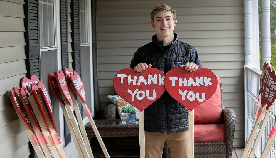 Mitchell Wollen, 16, of Wallingford shows some of the many wooden thank you signs his family is making and selling to donate snacks for local hospitals and nursing homes, Mon., Apr. 27, 2020. Dave Zajac, Record-Journal