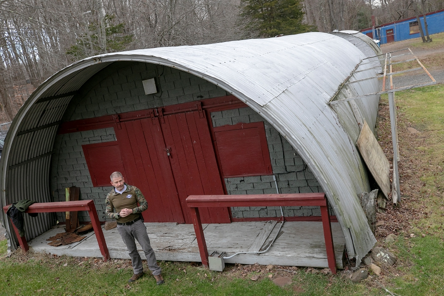 Kyle Overturf, general manager, stands in front of a Quonset hut used for storage at Blue Trail Range, 316 N. Branford Rd., Wallingford, Wed., Dec. 2, 2020. Blue Trail Range is plannning to construct a new maintenance and storage facility in the spring. Three Quonset huts and a one story building, top right, will be demolished as part of the project. Dave Zajac, Record-Journal