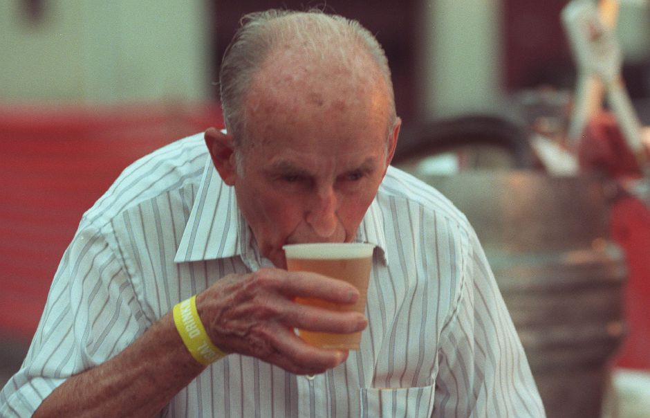 John Aszklar, of Plantsville, sips a beer as he walks back to his table from the tap at the Meriden Turner Society picnic at 800 Old Colony Road in Meriden July 17, 1999.