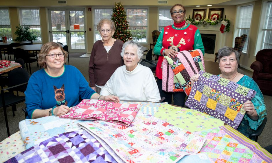 From left, Sue Vogt, Grace Lapita, Linda d'Hondt, Barbara Hanks and Lurene Ashlaw show the quilts they created for kids being treated at the Hospital for Special Care in New Britain.