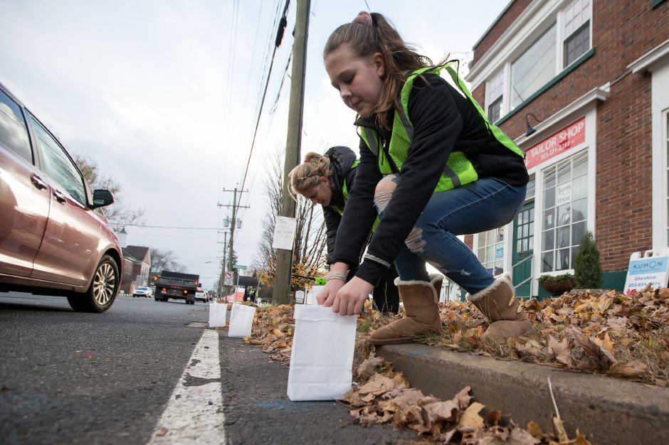 Ella Davis, 12, of Cheshire, sets a luminary along Route 10 on Saturday during the 14th Annual Cheshire Lights of Hope.