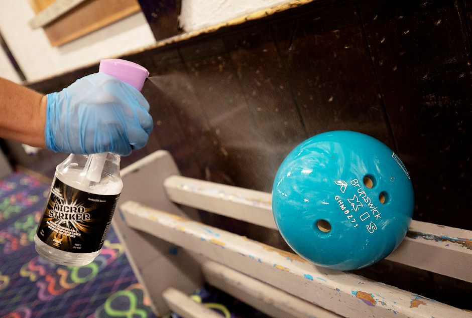 Manager Jason Scagliarini sprays down a house bowling ball with a multi-purpose cleaner at Lessard Lanes, 136 New Britain Ave., Plainville, Wed., Jul. 29, 2020. Most area alleys have opened back up and Lessard Lanes has made many adjustments to make their bowlers feel safe. Dave Zajac, Record-Journal