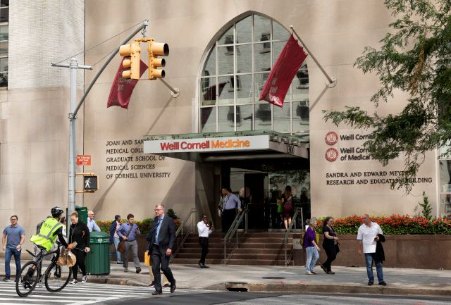 In this Sept. 26, 2019, photo, people pass the Weill Cornell Medicine center in New York. Prestigious universities around the world, including Cornell University, have accepted at least $60 million from the family that owns OxyContin maker Purdue Pharma over the past five years, even as the company has been embroiled in lawsuits over its role in the opioid epidemic, according to tax and charity records reviewed by The Associated Press. (AP Photo/Mark Lennihan)