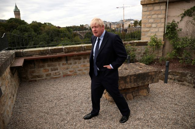 British Prime Minister Boris Johnson poses for photographers on the balcony of the UK ambassadors residence prior to giving a statement to television after a meeting with Luxembourg