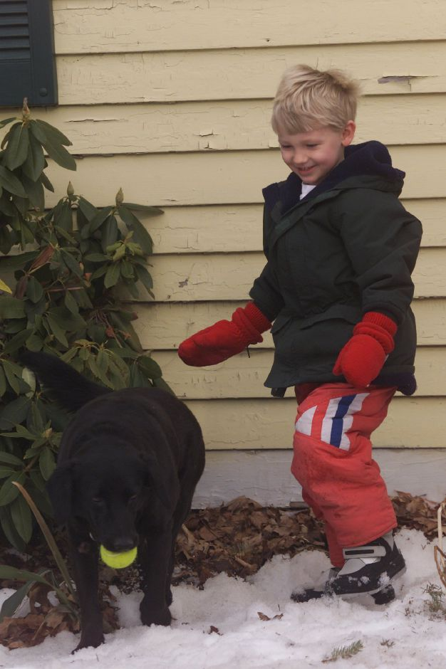 "Gabriel Van Ness, 4, of Meriden, plays a game of fetch with his black labrador retriever named ""Lady"" in front of his Atkins Street home Jan. 17, 2001."