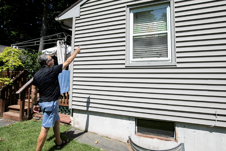 Mark Cirillo, of Meriden, points to one of several bullet holes that hit his 107 Allen Ave. residence after a fatal shooting stemming from an incident next door at 115 Allen Ave. Dave Zajac, Record-Journal