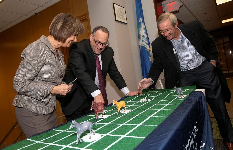 "FILE PHOTO —Tim Ryan, Economic Development Specialist, right, plays a little Kentucky Derby with Quinnipiac Chamber Executive Director Dee Prior-Nesti and Senior Director of Sales and Marketing Gary Ciarleglio during the 3rd Annual 4 Chamber Social ""Around the World"" hosted by the Record-Journal in Meriden, Thurs., Nov. 14, 2019. Dave Zajac, Record-Journal"