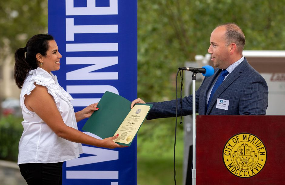Meriden Mayor Kevin Scarpati hands Maria Campos-Harlow, executive director of the United Way of Meriden and Wallingford, an official citation to celebrate the 90th anniversary of the United Way during the 2020-21 United Way of Meriden and Wallingford Award Ceremony and Community Campaign Kick-Off Event at the Meriden Green Amphitheater on Thursday, September 17, 2020. Aaron Flaum, Record-Journal