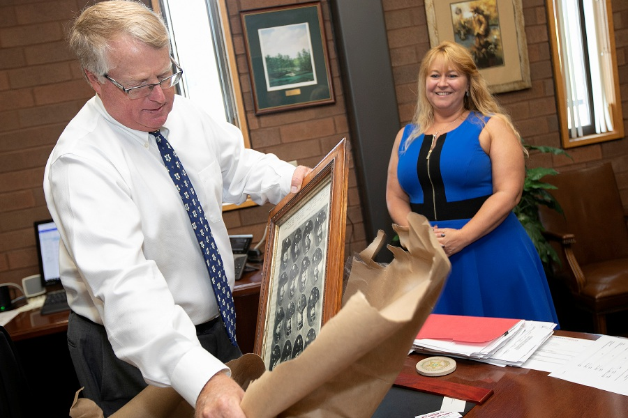 Chief Jeffry Cossette unwraps a 113-year-old framed photograph of police department members donated by Sheri DeLuca, right, in Cossette