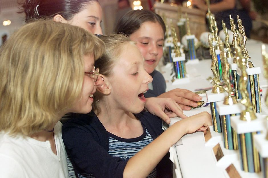 Crafty Lady teammates Brittany Pyskaty, left, 11, Tiffany Maxfield, 9, center, with Candace Massano, 11, top-left, and Brittany Bombardier, 10, top-right, look for their trophies at the Aqua Turf in Southington Mon. night, June 26, 2000 for the Wallingford Girls Softball League awards banquet.