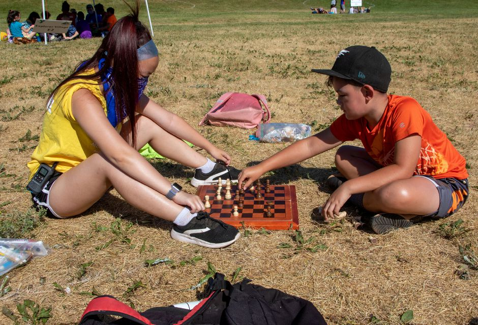 Camp counselor Nikki-Lee wears a mask as she paly chess with Robbie Chow 8, as they wait for morning announcements at the Meriden YMCA's Mountain Mist Day Camp on Friday, June 26, 2020. Aaron Flaum, Record-Journal
