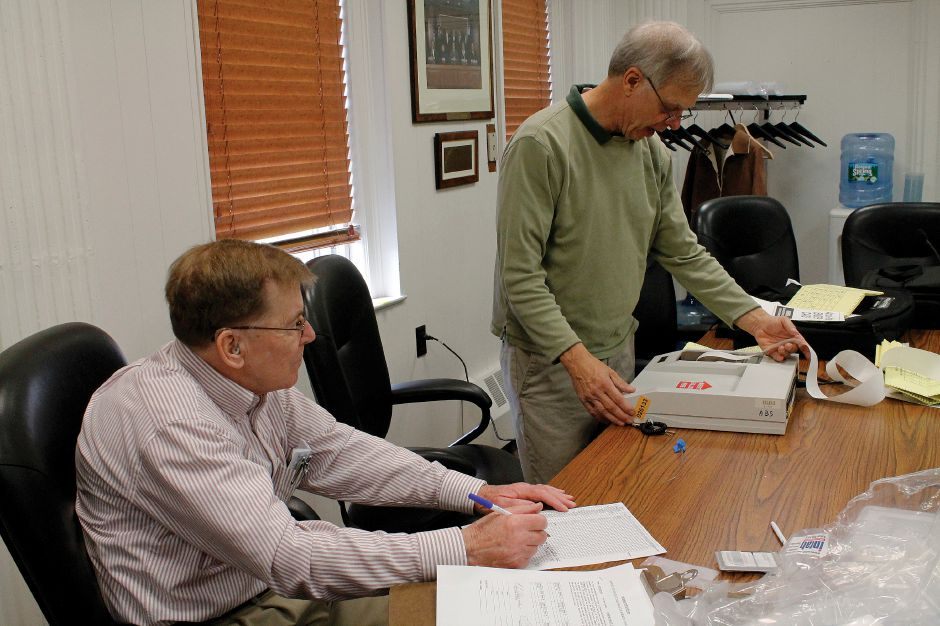 In preparations for election day, front, Robert Sherman and back, Edward Malczyk from the Registrar of Voters office, at the Southington Town Hall on Friday Nov. 2 2012, test the absentee ballot machine making sure it