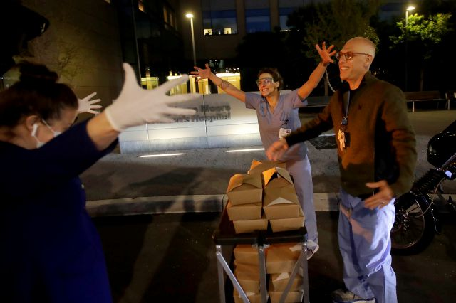 Nightbird Restaurant chef and owner Kim Alter, left, mimics giving a hug to nurse practitioner Sydney Gressel, center, and patient care technician Matt Phillips after delivering dinner to them at University of California at San Francisco Benioff Children