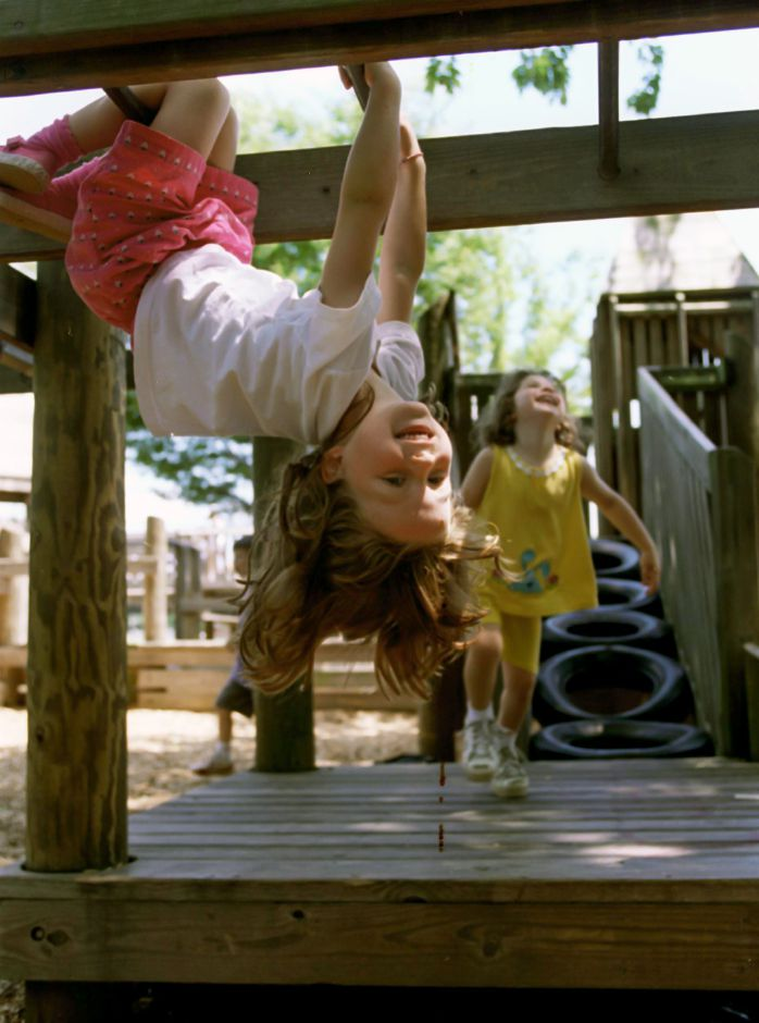 Alison Davis, 5, hangs from the bars at Doolittle Park in Wallingford on Wednesday, as her friend Rachael Pilletere,4, laughs at her friend hanging upside down June 28, 2000.