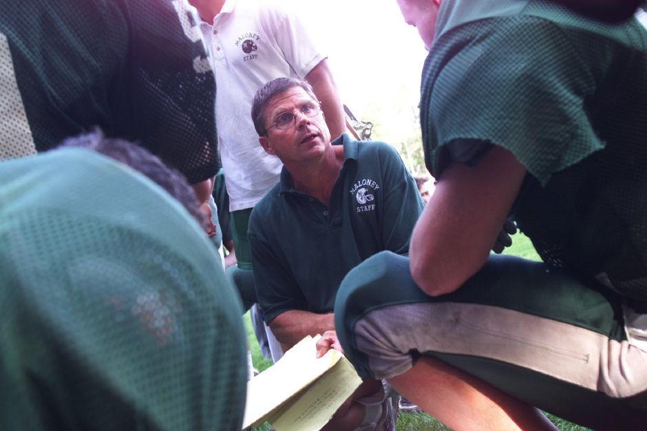 Maloney football coach Rob Szymaszek connects with his players during the halftime huddle of a scrimmage game against Cheshire High School on Sept. 1,1999.