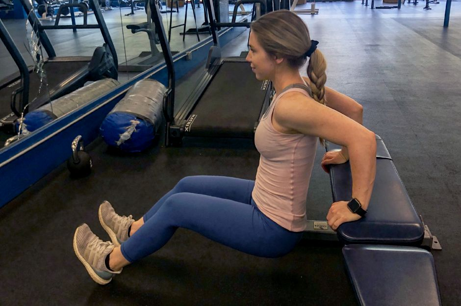 Kristen Dearborn demonstrates a tricep dip on a bench.