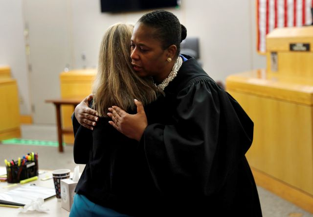 State District Judge Tammy Kemp gives former Dallas Police Officer Amber Guyger a hug before Guyger leaves for jail, Wednesday, Oct. 2, 2019, in Dallas. Guyger, who said she mistook neighbor Botham Jean