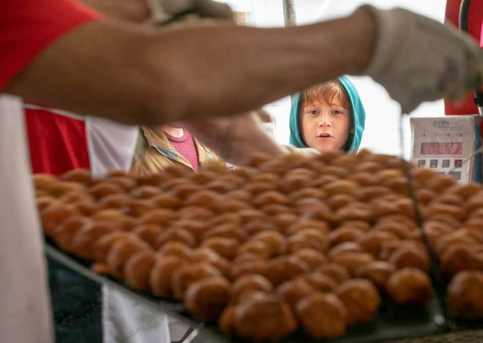 Dominick Napoletano, 11, of Southington, eyes a tray of freshly made fritters carried by volunteer Glenn Benoit, of Southington, at the Zion Lutheran Church Apple Fritter Booth in Southington, Tues., Oct. 8, 2019. Dave Zajac, Record-Journal