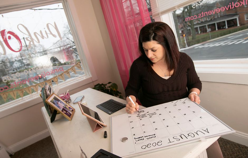 Event planner Carisa Lockery, owner of Pink Olive Events in Cheshire, on March 19 plans out a calendar of events for August, which includes postponements due to COVID-19. Dave Zajac, Record-Journal