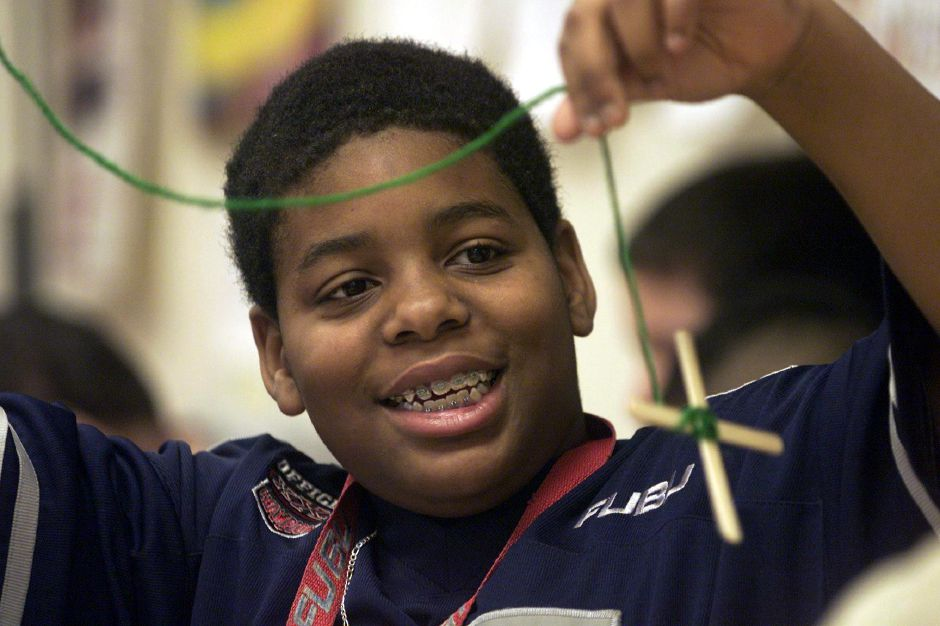 Jonathan Jenkins, a sixth grader at Washington Middle School in Meriden, shows off his progress on making a craft project to a friend Jan. 12, 2001. The sticks and yarn are weaved into a