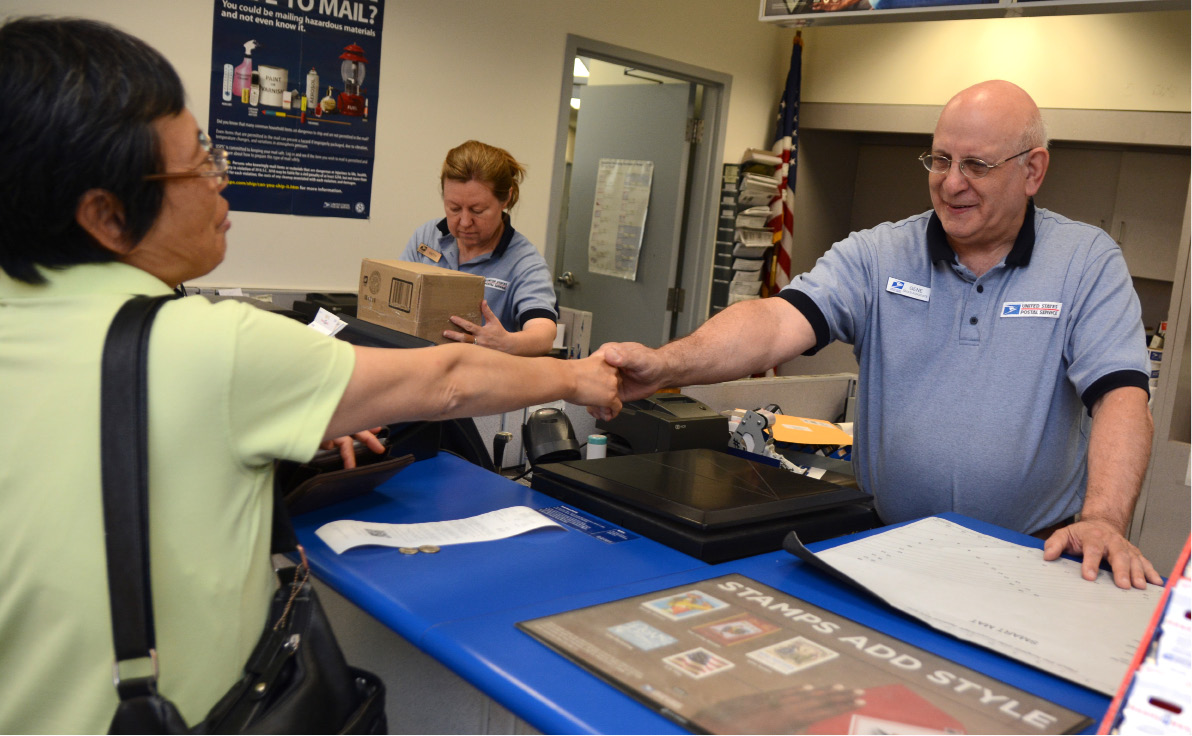 Meriden United States Postal Service clerk Gene Kirstens shakes hands with a customer at the post office on Thursday, June 15, 2017. | Bryan Lipiner, Record-Journal