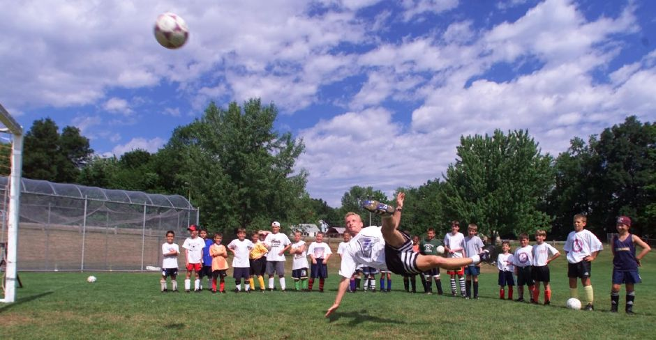 Rob Jachym, of Meriden, demonstrates a bicycle kick to his students at a soccer camp at Maloney Thursday morning July 8, 1999.