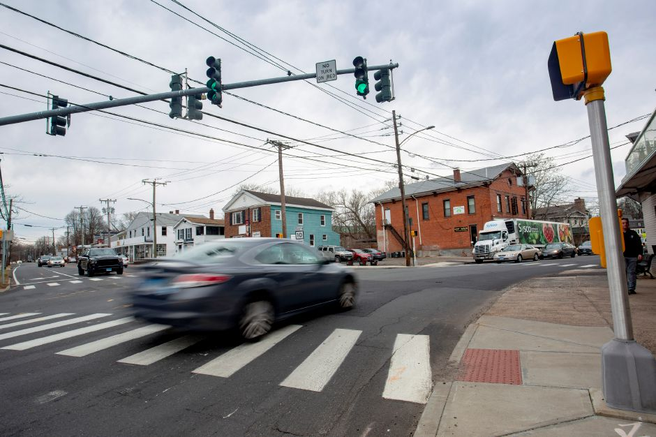 A car passes through the intersection of Route 10 and West Main Street in downtown Plantsville March 3, 2020. The brick building in the upper right, Hop Haus, has been struck by vehicles four times in the past few years by drivers trying to navigate the turn. | Richie Rathsack, Record-Journal