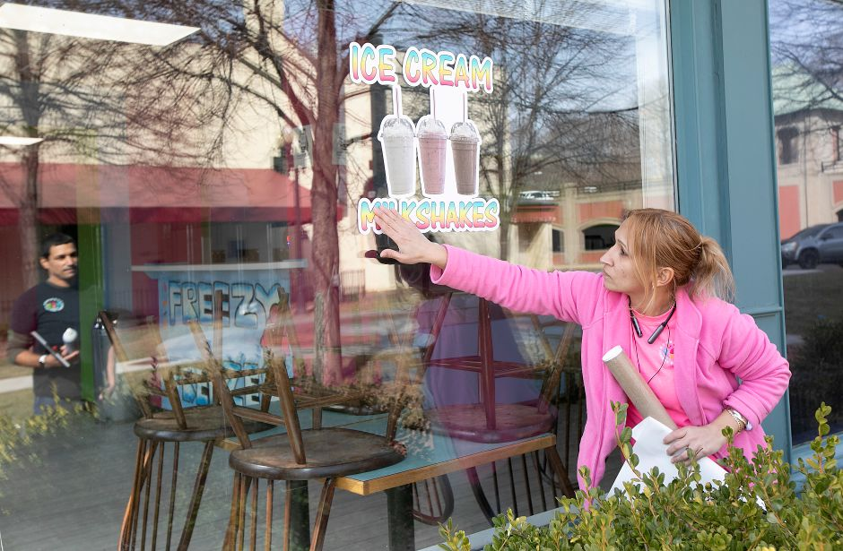 Downtown Freezy Freezes Gamestop co-owner Xiomara Alvarado adheres milkshake signage to the window of the 55 W. Main St. business in Meriden, Wed., Feb. 19, 2020. Co-owner Eddie Troche, left, can be seen in the reflection. The business now features ordering through Uber Eats. Dave Zajac, Record-Journal