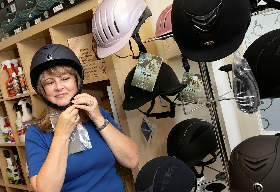 Carol DiCarlo, owner of Cheshire Equestrian Center, tries on a riding helmet at the new business at 116 S. Main St. in Cheshire. The store, opening Sept. 20, will offer clothing and riding equipment tailored largely to dressage riders. Dave Zajac, Record-Journal