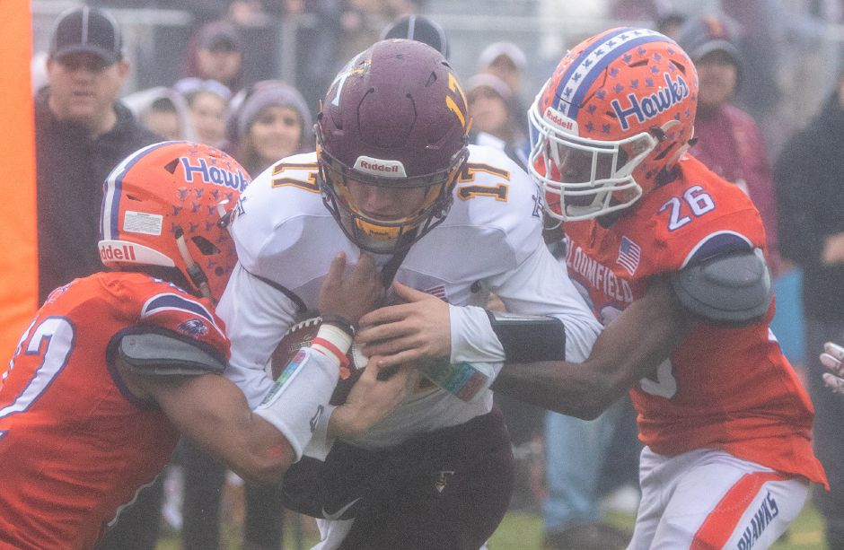 Sheehan's Kyle Simmons is taken down by Bloomfield's Denzel Patrick and Shakur Hill during the CIAC Class S Championship Football game at Trumbull High School. Aaron Flaum, Record-Journal