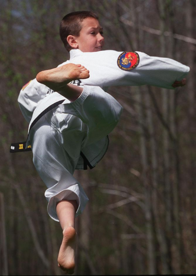 Rian Sullivan demonstrates a flying kick in his backyard. Rian Sullivan, 10, of Wallingford just got his second degree black belt in TaeKwon-Do, April 25, 2000.