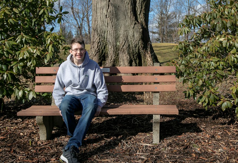 Blake Kunst, of Meriden, sits on a bench in a memorial garden he created in honor of his grandfather Carlos Lavado at Hunter Golf Course in Meriden, Thurs., Feb. 27, 2020. The 19-year-old diagnosed with Autism Spectrum Disorder is a maintenance worker at the course on Westfield Road. Kunst constructed the garden as part of his Eagle Scout project in 2018. Dave Zajac, Record-Journal