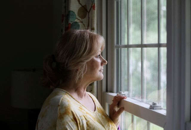 In this Friday, Sept. 13, 2019, photo, Denise Spence poses for a photograph by the window of her home in Palatine, Ill. Spence said her son Timothy died of an opioid overdose. While the nation