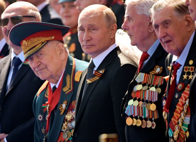 FILE - In this June 24, 2020, file photo, Russian President Vladimir Putin, center, watches the Victory Day military parade marking the 75th anniversary of the Nazi defeat in Moscow. Putin is just a step away from bringing about the constitutional changes that would allow him to extend his rule until 2036. The vote that would reset the clock on Putin's tenure in office and allow him to serve two more six-year terms is set to wrap up Wednesday, July 1, 2020. (Sergei Guneyev/Host Photo...