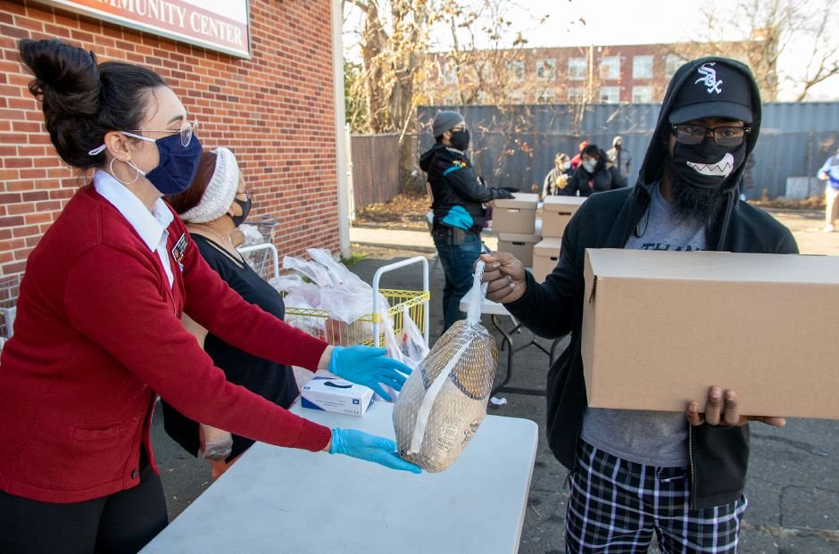 Salvation Army's Lt. Corps Officer Kate Borrero hands Mike Ransom of Meriden a turkey as Thanksgiving meals are distributed to families at the Meriden Salvation Army on Friday, November 20, 2020. Aaron Flaum, Record-Journal