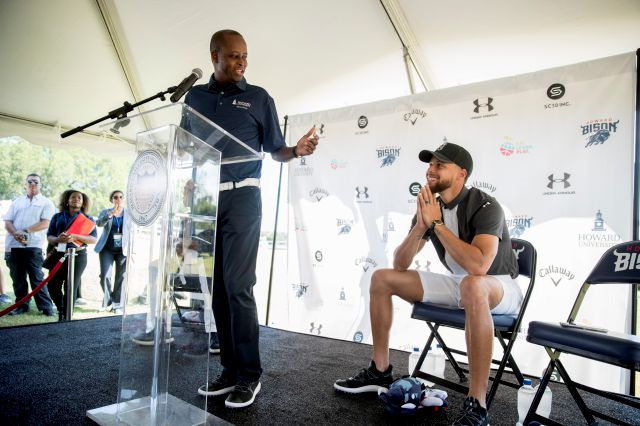 Howard University president Wayne Frederick, left, looks at Golden State Warriors guard Stephen Curry during a news conference at Langston Golf Course in Washington, Monday, Aug. 19, 2019, where Curry announced that he would be sponsoring men
